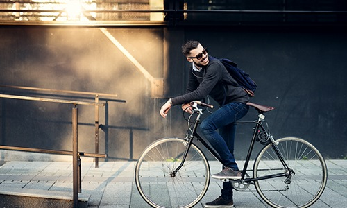 A man sits on his bike in front of a cafe.