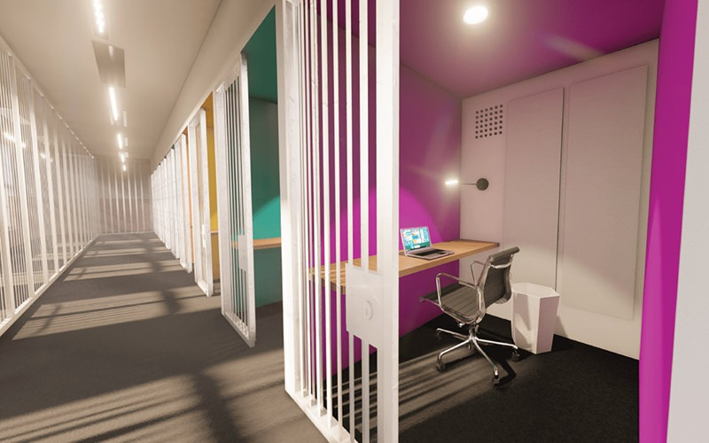 Refurbished pink and green jail-cells that are turned into personal work spaces.