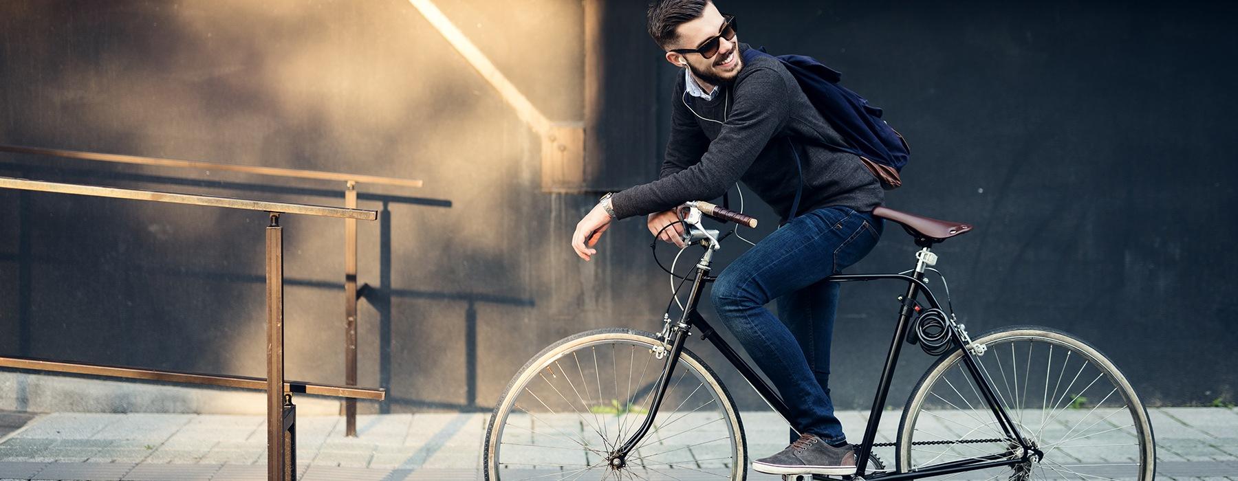 A man is sitting on his bike on a sidewalk